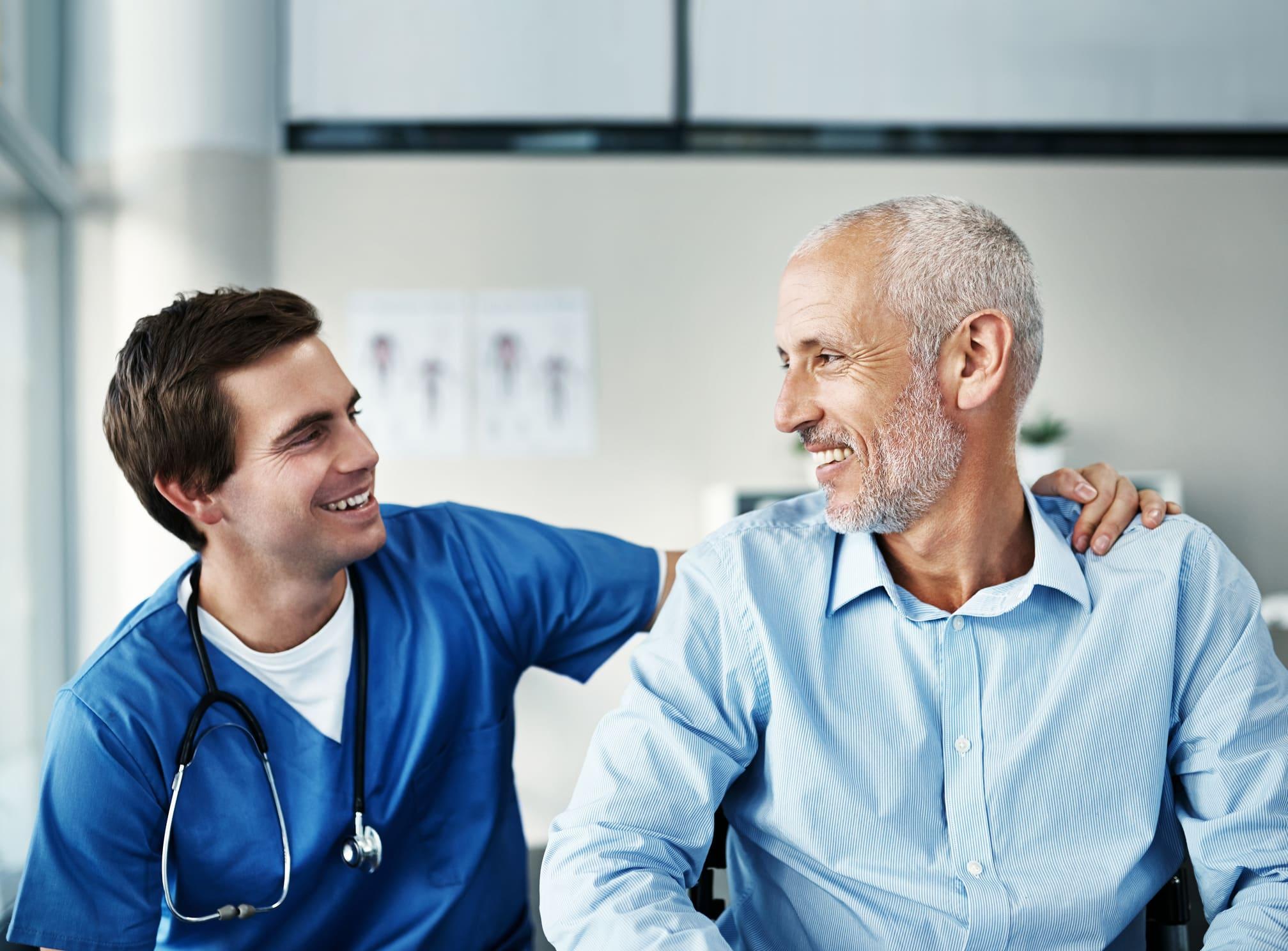 a male nurse attending an old man patient